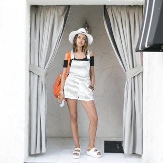 Come indossare e abbinare: top corto nero, salopette corta di jeans a righe verticali bianca, sandali piatti in pelle bianchi, zaino in pelle arancione