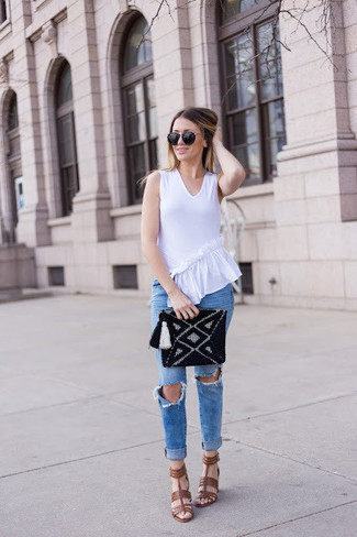Come indossare: top senza maniche con volant bianco, jeans aderenti strappati blu, sandali con tacco in pelle marroni, pochette lavorata a maglia nera