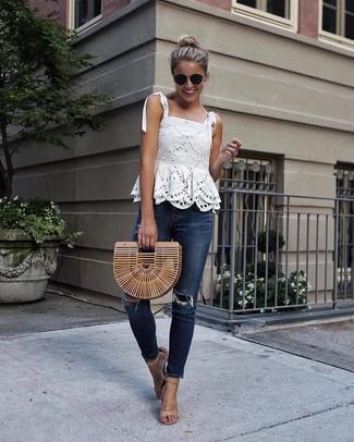 Come indossare: top senza maniche di pizzo bianco, jeans aderenti strappati blu scuro, sandali con tacco in pelle marrone chiaro, pochette di paglia marrone chiaro