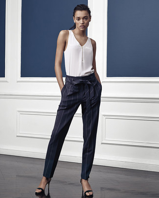 Come indossare e abbinare: top senza maniche di seta bianco, pantaloni stretti in fondo a righe verticali blu scuro, sandali con tacco in pelle neri