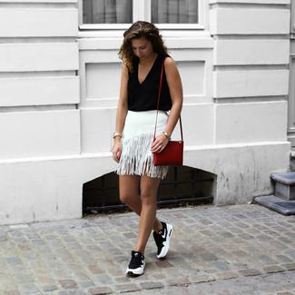 Come indossare: top senza maniche nero, minigonna con frange bianca, scarpe sportive nere e bianche, borsa a tracolla in pelle rossa