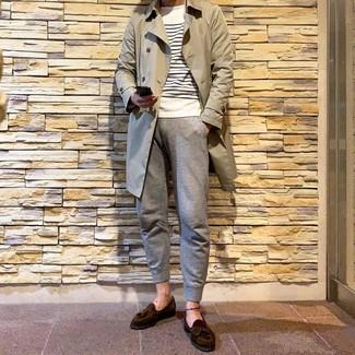 Come indossare e abbinare: trench beige, maglione girocollo a righe orizzontali bianco e blu scuro, pantaloni sportivi grigi, mocassini con nappine in pelle scamosciata marrone scuro