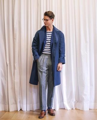 Come indossare e abbinare: trench blu scuro, blazer di lana blu scuro, t-shirt girocollo a righe orizzontali bianca e blu scuro, pantaloni eleganti di lana grigi