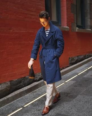 Come indossare e abbinare: trench blu scuro, t-shirt girocollo a righe orizzontali bianca e blu scuro, pantaloni eleganti di lino beige, mocassini eleganti in pelle marroni