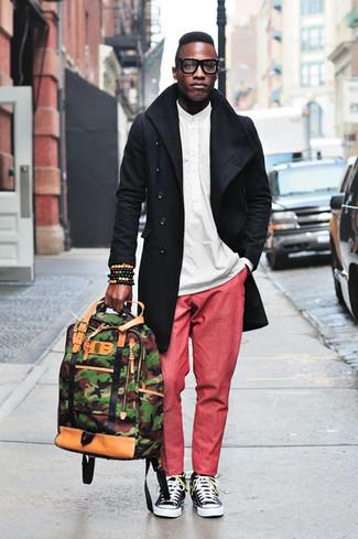 Come indossare e abbinare: trench nero, camicia a maniche lunghe bianca, chino rossi, sneakers basse di tela nere e bianche