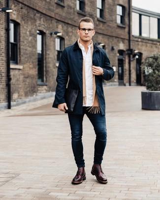 Come indossare e abbinare: trench blu scuro, camicia a maniche lunghe bianca, jeans aderenti blu scuro, scarpe brogue in pelle bordeaux