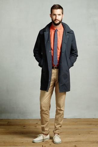 Come indossare e abbinare: trench nero, camicia elegante arancione, chino marrone chiaro, sneakers basse di tela beige