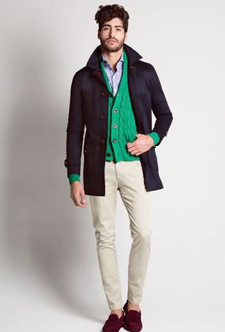 Come indossare e abbinare: trench nero, cardigan con collo a scialle verde, camicia a maniche lunghe azzurra, chino beige