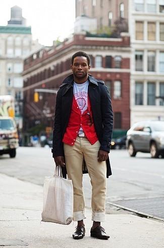 Come indossare e abbinare: trench nero, cardigan rosso, t-shirt girocollo stampata bianca e rossa, chino marrone chiaro