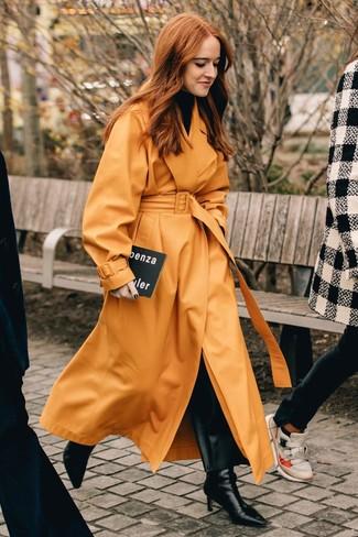 Come indossare: trench in pelle arancione, dolcevita nero, pantaloni larghi in pelle neri, stivaletti in pelle neri