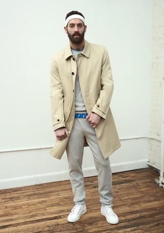 Come indossare e abbinare: trench marrone chiaro, felpa grigia, t-shirt girocollo stampata blu, pantaloni sportivi grigi
