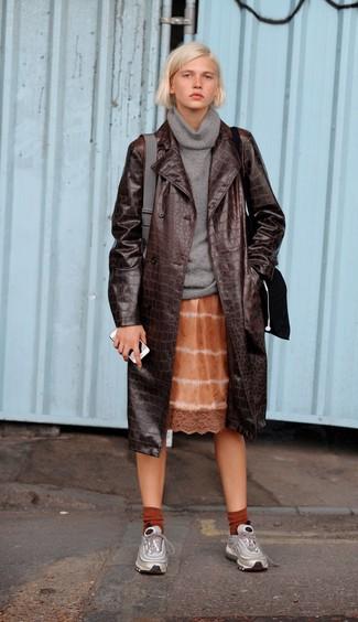 Come indossare: trench in pelle marrone scuro, maglione con scollo a cappuccio grigio, sottoveste effetto tie-dye arancione, scarpe sportive argento
