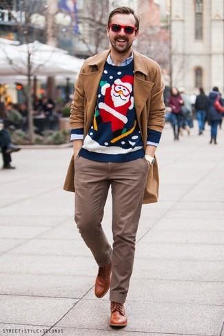 Come indossare e abbinare: trench marrone chiaro, maglione girocollo di natale blu scuro, camicia a maniche lunghe azzurra, chino marroni