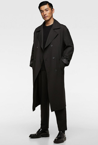 Come indossare e abbinare: trench nero, maglione girocollo nero, chino neri, scarpe derby in pelle nere