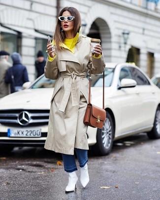 Come indossare: trench beige, maglione girocollo giallo, jeans blu, stivaletti in pelle bianchi