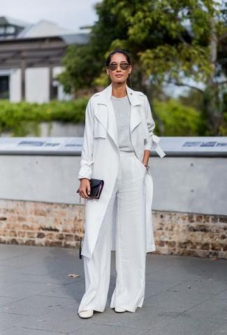 Come indossare: trench grigio, maglione girocollo grigio, pantaloni larghi bianchi, décolleté in pelle bianchi