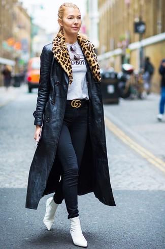 Come indossare: trench in pelle nero, t-shirt girocollo stampata grigia, jeans aderenti neri, stivaletti elasticizzati bianchi