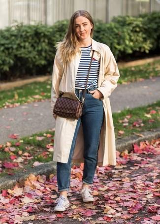 Come indossare: trench beige, t-shirt girocollo a righe orizzontali bianca e blu scuro, jeans blu scuro, sneakers basse di tela bianche