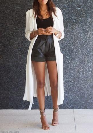 Come indossare: trench leggero bianco, top corto nero, pantaloncini in pelle neri, sandali con tacco in pelle beige