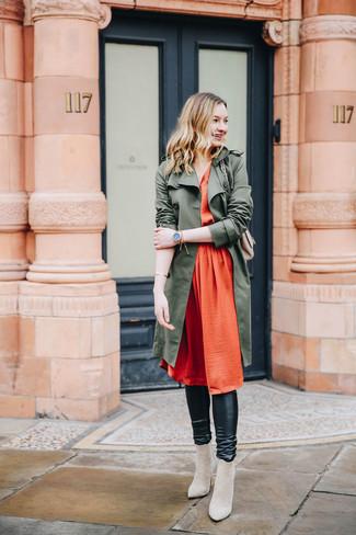 Come indossare e abbinare: trench verde oliva, vestito longuette di seta a pieghe arancione, leggings in pelle neri, stivaletti in pelle scamosciata beige