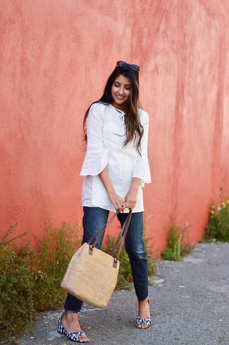 Come indossare: tunica bianca, jeans blu scuro, sandali con tacco di tela a quadretti blu scuro e bianchi, borsa shopping di paglia marrone chiaro