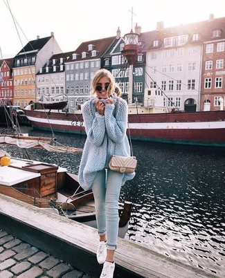 Come indossare: tunica lavorata a maglia azzurra, jeans aderenti azzurri, sneakers basse in pelle bianche, borsa a tracolla in pelle trapuntata beige