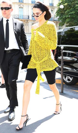 Come indossare: tunica lavorata a maglia gialla, pantaloncini ciclisti neri, sandali con tacco in pelle neri, pochette in pelle scamosciata nera