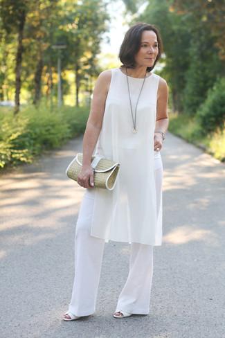 Come indossare: tunica di seta bianca, pantaloni larghi bianchi, sandali con tacco in pelle bianchi, pochette di paglia marrone chiaro