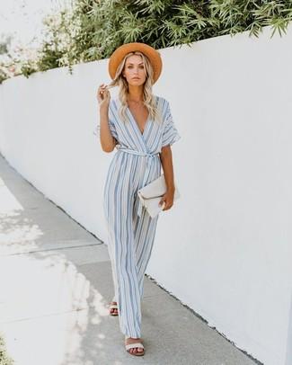 Come indossare: tuta a righe verticali azzurra, sandali piatti in pelle bianchi, pochette in pelle bianca, borsalino di paglia marrone chiaro
