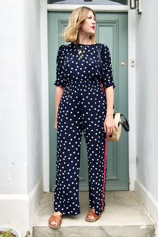 Come indossare e abbinare: tuta a pois blu scuro, sandali piatti in pelle marroni, borsa a tracolla di paglia beige, collana con ciondolo dorata