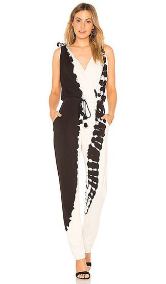 Come indossare: tuta effetto tie-dye nera e bianca, sandali con tacco in pelle scamosciata neri, orecchini dorati