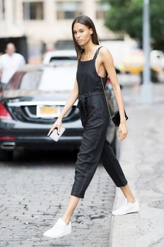 Come indossare: tuta nera, sneakers basse in pelle bianche, borsa a tracolla in pelle nera