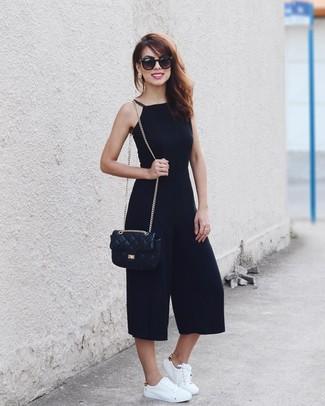 Come indossare: tuta nera, sneakers basse in pelle bianche, borsa a tracolla in pelle trapuntata nera, occhiali da sole neri