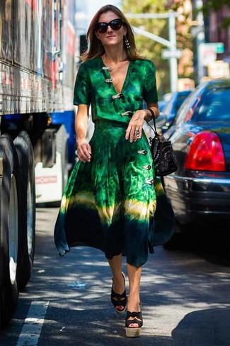 Come indossare: vestito a portafoglio effetto tie-dye verde, sandali con zeppa di tela neri, borsa a secchiello in pelle scamosciata con borchie nera
