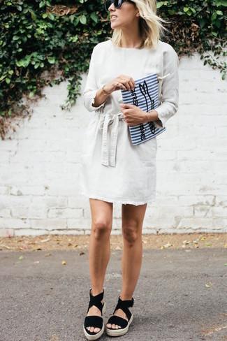 Trend da donna 2020: Mostra il tuo stile in un vestito a trapezio bianco se preferisci uno stile ordinato e alla moda. Non vuoi calcare troppo la mano con le scarpe? Prova con un paio di sandali con zeppa in pelle scamosciata neri per la giornata.