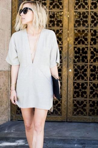 Come indossare: vestito a trapezio grigio, pochette in pelle nera, occhiali da sole neri