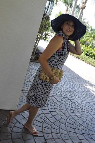 Come indossare: vestito a trapezio stampato blu scuro, infradito dorati, pochette di paglia marrone chiaro, borsalino di paglia blu scuro