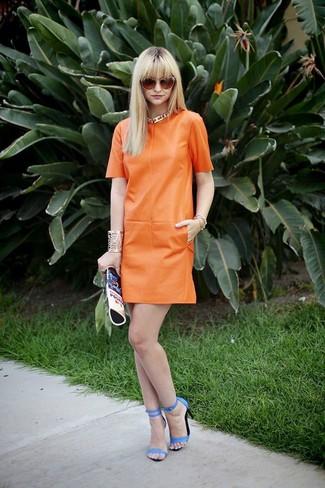 Come indossare: vestito a trapezio in pelle arancione, sandali con tacco in pelle blu, pochette in pelle stampata blu, occhiali da sole arancioni