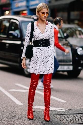 Come indossare: vestito chemisier a pois bianco e nero, stivali sopra il ginocchio in pelle rossi, borsa a tracolla di pelliccia nera, cintura a vita alta nera