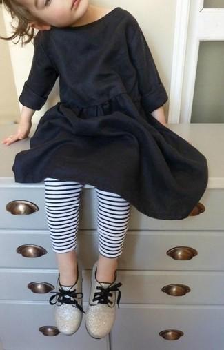 Come indossare: vestito di cotone nero, leggings a righe orizzontali bianchi e neri, scarpe oxford dorate