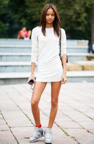 Come indossare e abbinare sneakers con zeppa in pelle grigie: Indossa un vestito di maglia bianco per essere trendy e seducente. Non vuoi calcare troppo la mano con le scarpe? Mettiti un paio di sneakers con zeppa in pelle grigie per la giornata.