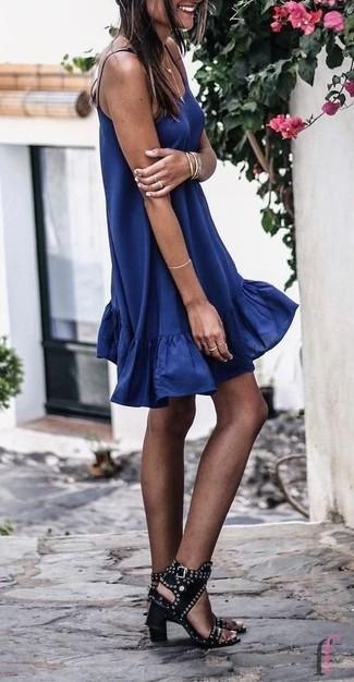 Come indossare: vestito scampanato blu scuro, sandali con tacco in pelle con borchie neri, bracciale dorato