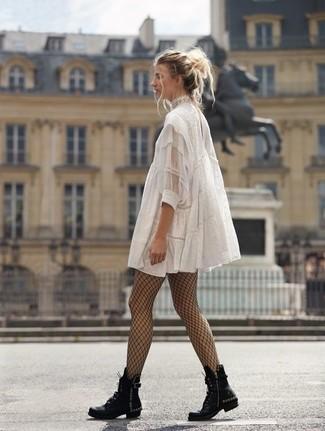 Come indossare: vestito scampanato di pizzo bianco, stivali piatti stringati in pelle con borchie neri, collant a rete nero