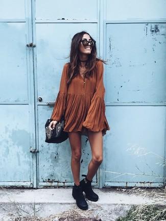 Come indossare: vestito scampanato terracotta, stivaletti in pelle neri, borsa a secchiello in pelle decorata nera, occhiali da sole neri e dorati