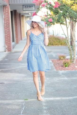 Come indossare: vestito svasato a quadretti azzurro, sandali con tacco in pelle scamosciata beige, borsalino di paglia bianco, bracciale bianco