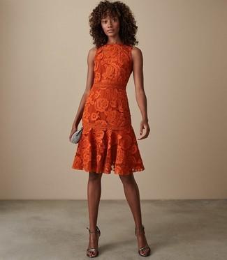 Come indossare: vestito svasato di pizzo arancione, sandali con tacco in pelle argento, pochette decorata argento