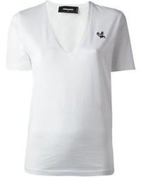 Una minigonna in pelle nera e una t-shirt con scollo a v per essere spensierata e alla moda.